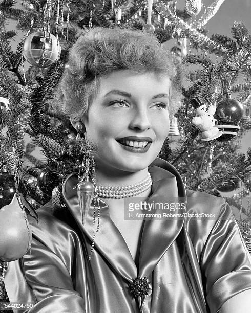 1940s 1950s PORTRAIT SMILING WOMAN WITH CHRISTMAS TREE WEARING SATIN BLOUSE PEARL NECKLACE