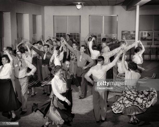 1940s 1950s ROOM FULL OF COUPLES MEN AND WOMEN WEARING WESTERN ATTIRE SQUARE DANCING