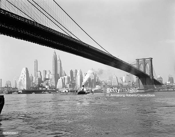 1940s 1950s SKYLINE OF LOWER MANHATTAN WITH BROOKLYN BRIDGE FROM BROOKLYN ACROSS THE EAST RIVER