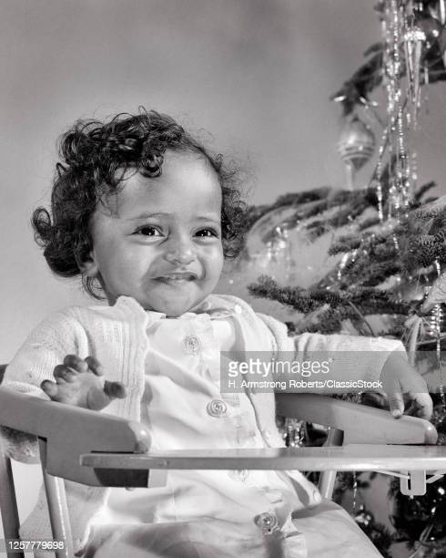 1940s 1950s Smiling African-American Baby Girl In High Chair Beside Christmas Tree