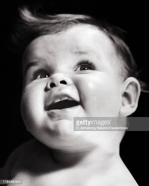 1940s 1950s SMILING BABY SHOWING TWO FRONT TEETH HEAD TILTED LOOKING UP
