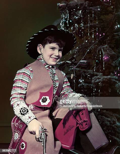 1940s 1950s SMILING BOY DRESSED IN COWBYO HAT COSTUME HOLDING TOY GUN SITTING WOODEN HORSE BY CHRISTMAS TREE