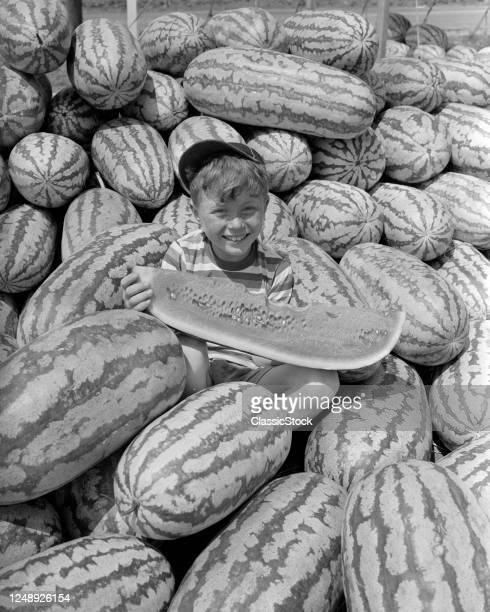 1940s 1950s Smiling Boy Wearing Ball Cap Looking At Camera Sitting In Pile Of Watermelons Eating A Large Slice Of One
