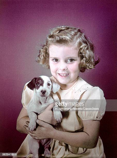 1940s 1950s SMILING GIRL HOLDING SPOTTED PUPPY