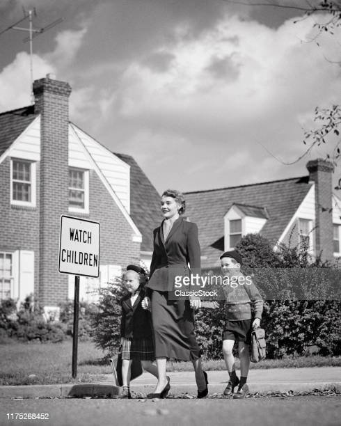 1940s 1950s SMILING WOMAN MOTHER WEARING SUIT WALKING TWO CHILDREN BOY GIRL TO SCHOOL CROSSING STREET BY WATCH CHILDREN SIGN