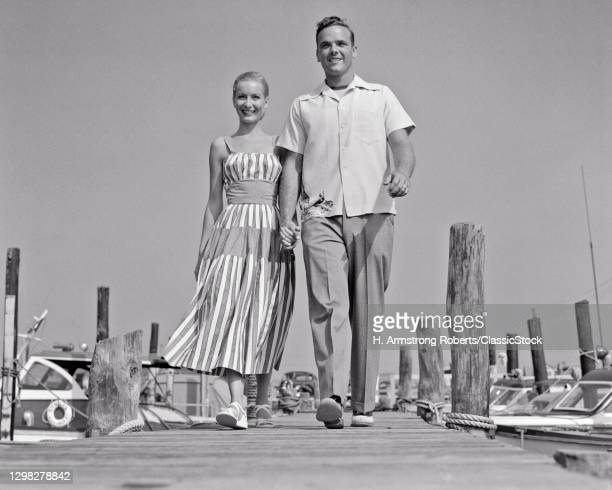 1940s 1950s Smiling Young Couple Man Woman In Summer Stylish Clothes Walking Down Wooden Dock At Power Boat Marina Holding Hands.