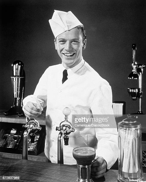 1940s 1950s SMILING YOUNG MAN SODA JERK AT COUNTER SERVING AN ICE CREAM SODA LOOKING AT CAMERA