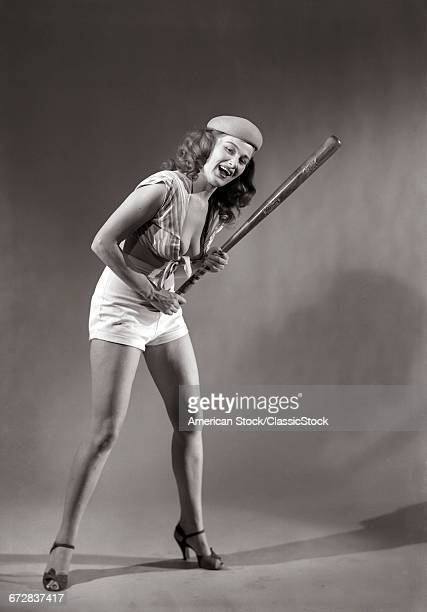 1940s 1950s SMILING WOMAN WEARING HALTER TOP SHORT SHORTS HOLDING BASEBALL BAT LOOKING AT CAMERA