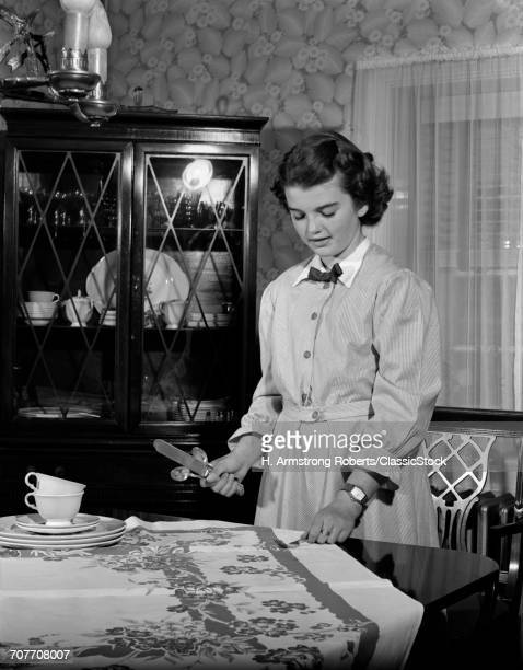 1940s 1950s TEEN GIRL SETTING THE TABLE IN DINING ROOM