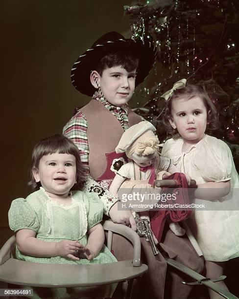 1940s 1950s THREE CHILDREN BY CHRISTMAS TREE BOY COWBOY HAT COSTUME GIRL WITH DOLL TODDLER IN CHAIR