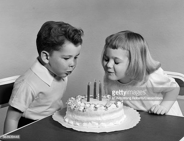 1940s 1950s TWO CHILDREN BLOWING OUT BIRTHDAY CANDLES