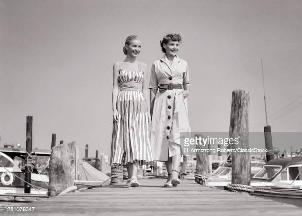 1940s 1950s Two Smiling Women Sisters Wearing Stylish Summer Dresses Walking Along Wooden Boat Dock At Seashore