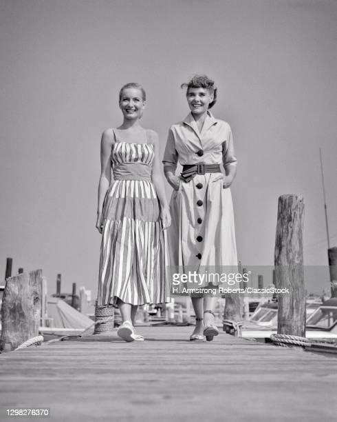 1940s 1950s Two Smiling Young Women Wearing Stylish Summer Dresses Walking Side-By-Side On Wooden Boat Dock At A Marina.
