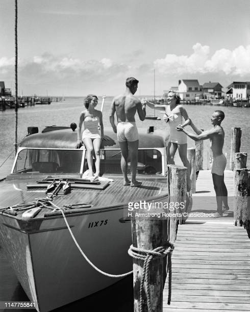 1940s 1950s TWO YOUNG COUPLES MEN WOMEN WEARING BATHING SUITS BOARDING SMALL CABIN CRUISER POWER BOAT MOORED BAY SIDE AT DOCK