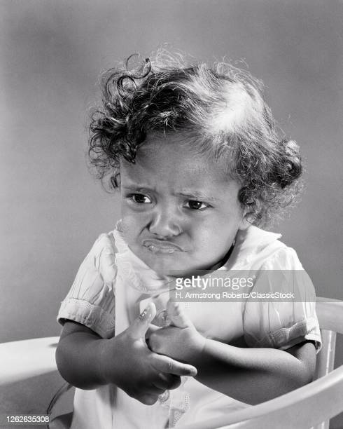 1940s 1950s Very Unhappy AfricanAmerican Baby Girl Sitting Wringing Her Hands With Angry Sad Mad Facial Expression
