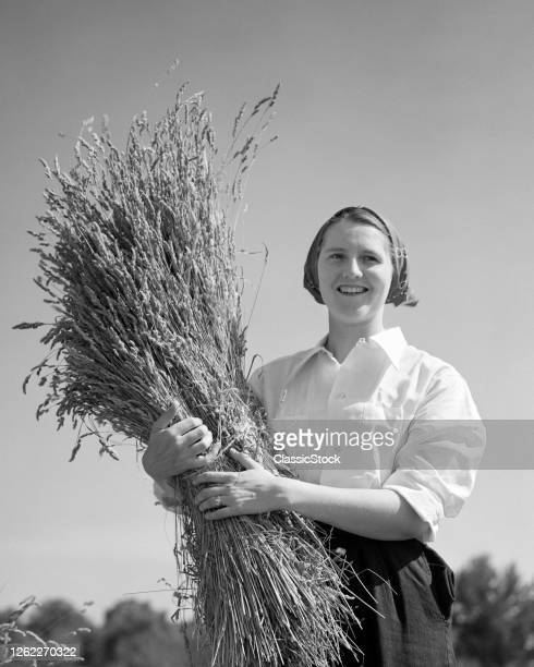 1940s 1950s Wholesome Healthy Smiling Farm Woman Holding A Sheaf Armful Of Bundled Wheat Stalks