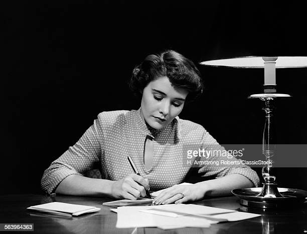 1940s 1950s WOMAN AT DESK IN EVENING WRITING CHECK PAYING BILLS WORKING ON BUDGET