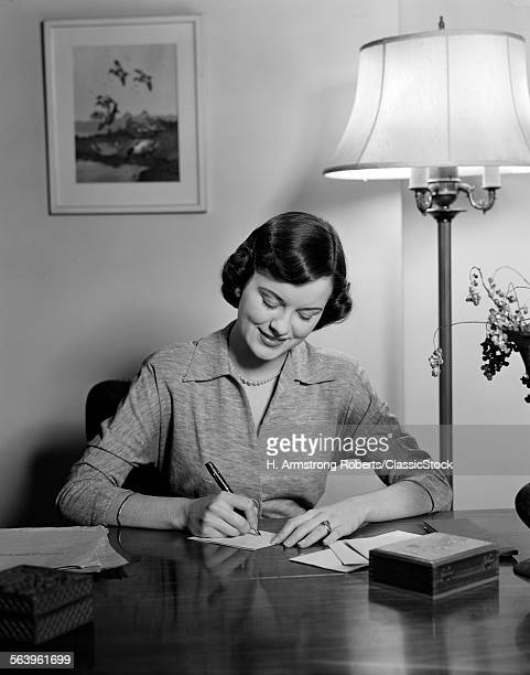 1940s 1950s WOMAN SITTING AT DESK WRITING LETTERS DOING CORRESPONDENCE