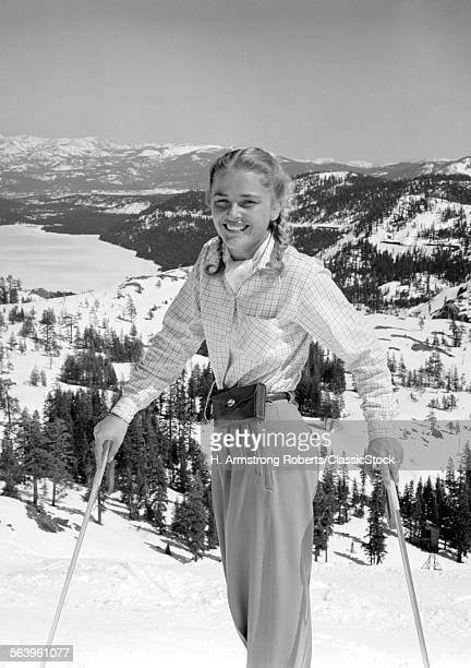 1940s 1950s YOUNG BLOND ATHLETIC WOMAN LOOKING AT CAMERA SMILING STANDING WITH SKI POLES TOP OF MOUNTAIN