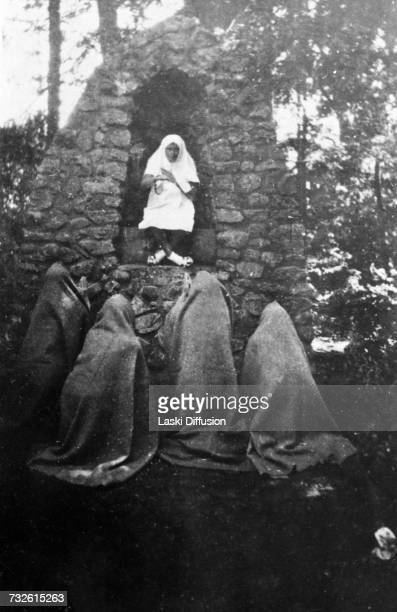 A desecration Germans indulging in horseplay at a roadside shrine in keeping with their programme to eradicate the Catholic church from the culture...