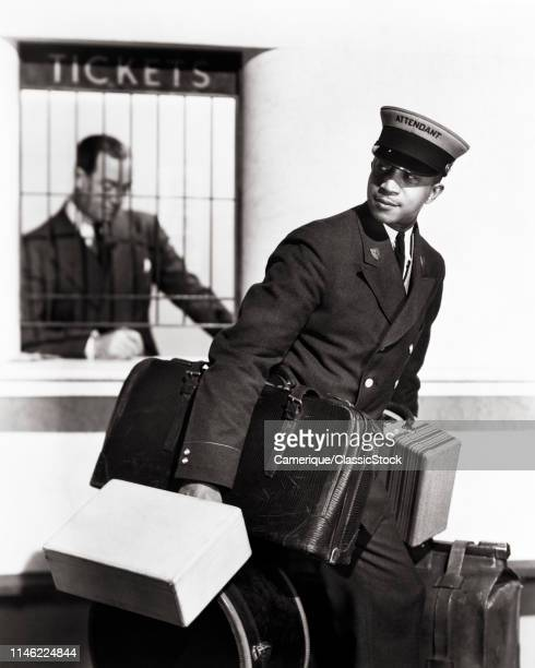 1940s AFRICAN AMERICAN MAN PORTER ATTENDANT CARRYING LUGGAGE IN RAILROAD TRAIN STATION