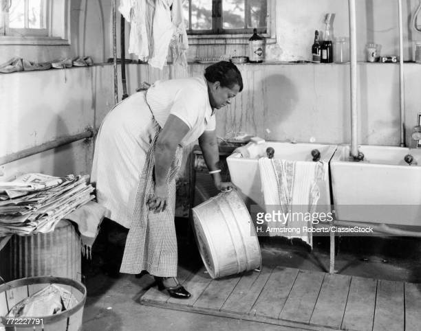 1940s AFRICAN AMERICAN OVERWEIGHT WOMAN STOOPING IN LAUNDRY ROOM PICKING UP GALVANIZED WASH TUB