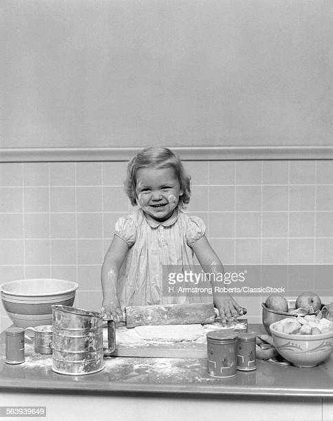 1940s BLOND GIRL BAKING PLAYING ROLLING PIN FLOUR DOUGH LOOKING AT CAMERA