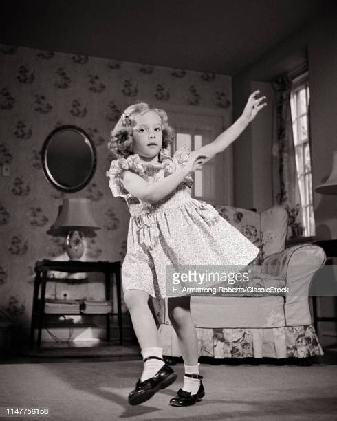 1940s BLOND GIRLIN DRESS WEARING MARY JANE SHOES LOOKING AT CAMERA DANCING HOKEY-POKEY IN LIVING ROOM
