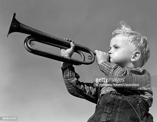 1940s BOY BLOWING BUGLE...