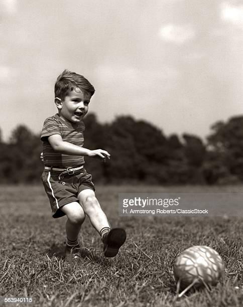 1940s BOY KICKING BALL IN...
