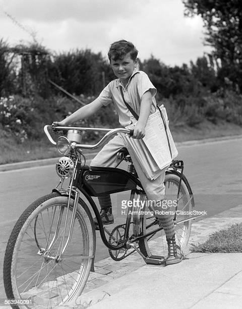 1940s BOY ON AN ELGIN BIKE CARRYING NEWSPAPERS IN A SLING WEARING KNEE SOCKS AND SNEAKERS