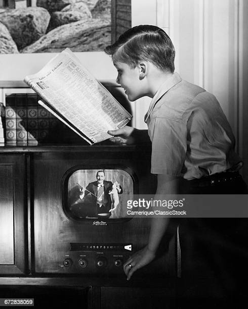 1940s BOY READING NEWSPAPER TV GUIDE ADJUSTING HIS TELEVISION TO CORRECT CHANNEL