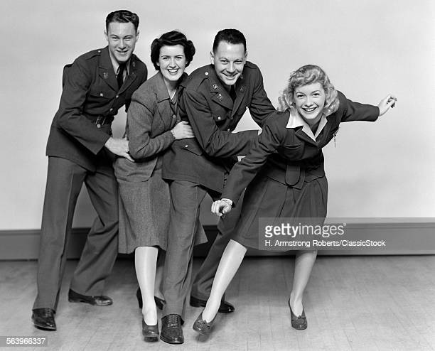 1940s CONGA LINE TWO MEN SOLDIERS AND TWO WOMEN DANCING SMILING LOOKING AT CAMERA