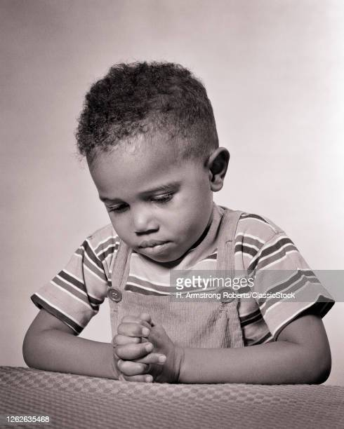 1940s Devout Serious Young AfricanAmerican Boy Wearing TShirt And Overalls Kneeling Saying His Prayers