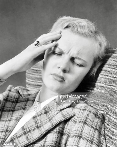 1940s distressed blond woman hand to her forehead pained expression eyes closed suffering headache pain
