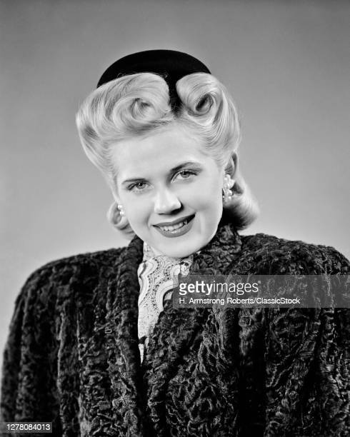 1940s Elegant Blond Woman With Very Big Victory Rolls Hair Style Looking At Camera Wearing Black Persian Lamb Coat