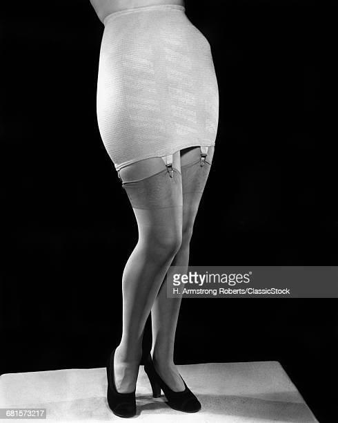 1940s FASHION WOMAN FROM WAIST DOWN WEARING GIRDLE WITH GARTERS CLIPS HOLDING SILK NYLON HOSE STOCKINGS