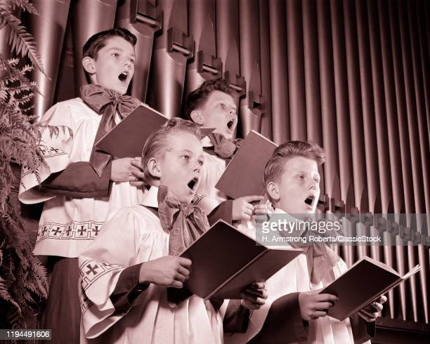 1940s FOUR CHOIRBOYS SINGING TOGETHER HOLDING HYMN BOOKS STANDING IN FRONT OF CHURCH ORGAN PIPES