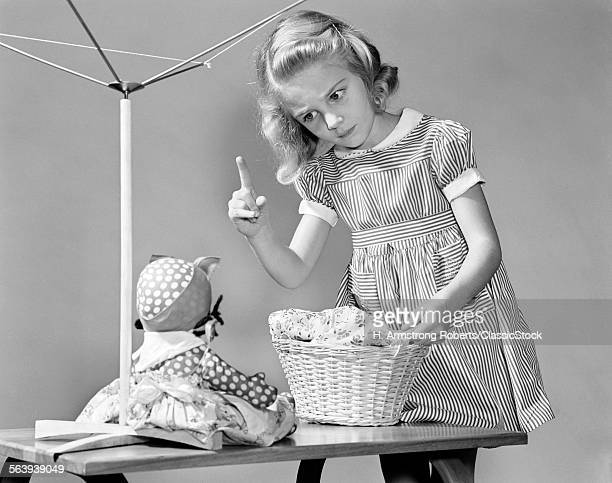 1940s GIRL SHAKING HER FINGER AT DOLL OVER TOY LAUNDRY BASKET
