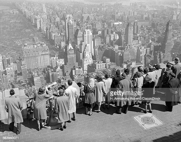 1940s GROUP OF ANONYMOUS TOURISTS STANDING ON TOP OF RCA BUILDING LOOKING NORTH TOWARDS MANHATTAN CENTRAL PARK NYC NY USA