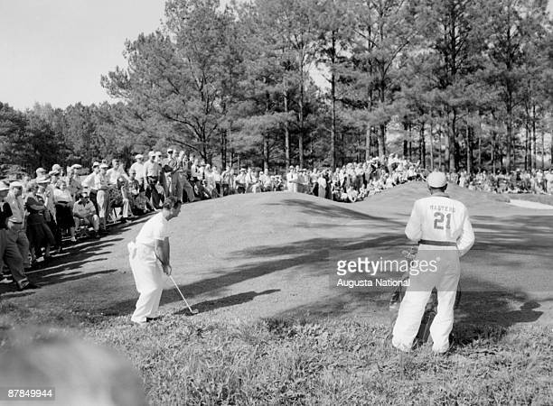 1940s: Jimmy Demaret chips onto the green as his caddie and a large gallery watch during a 1940s Masters Tournament at Augusta National Golf Club in...