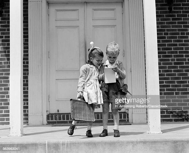 1940s LITTLE BOY AND GIRL WITH SCHOOL BAGS LOOKING AT NOTEPAD OUTDOOR