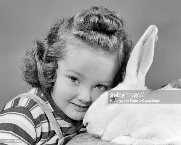 1940s Little Girl Looking At Camera Head To Head With A White Rabbit