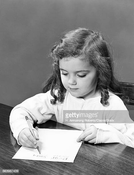1940s LITTLE GIRL WITH CURLY HAIR WRITING LETTER WITH PENCIL AND PAPER