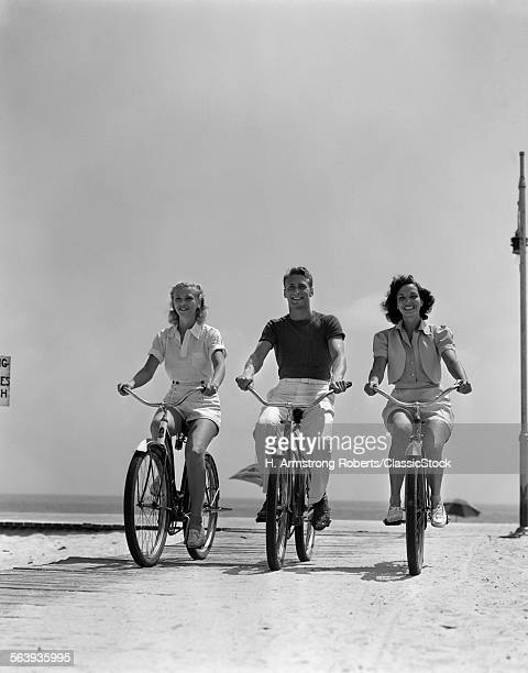 1940s MAN TWO WOMEN BIKING...