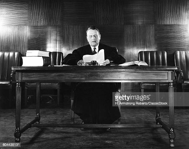 1940s MALE JUDGE READING PAPERS WEARING ROBE SEATED AT DESK