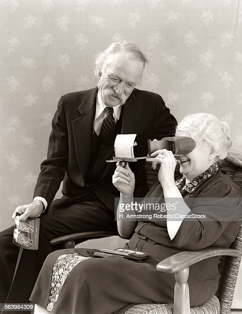 1940s OLDER SENIOR COUPLE MAN WOMAN VIEWING PHOTOGRAPHS BY STEREOPTICON STEREOSCOPE