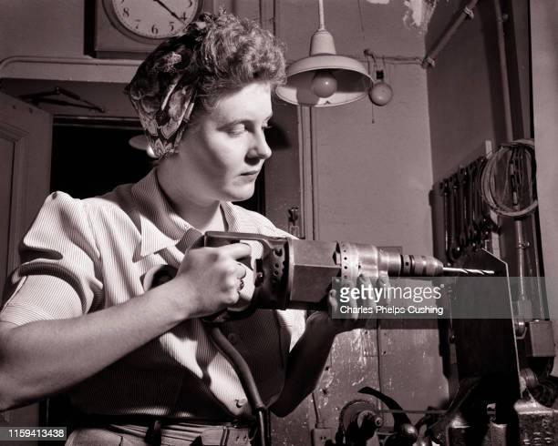 1940s PATRIOTIC ANONYMOUS UNIDENTIFIED WOMAN HOME FRONT INDUSTRIAL WORKER USING ELECTRICAL HAND DRILL DURING WORLD WAR II