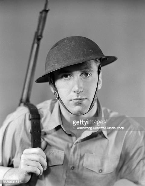 1940s PORTRAIT OF AMERICAN SOLDIER RIFLE ON SHOULDER HELMET WITH CHIN STRAP PIERCING SERIOUS EXPRESSION LOOKING AT CAMERA