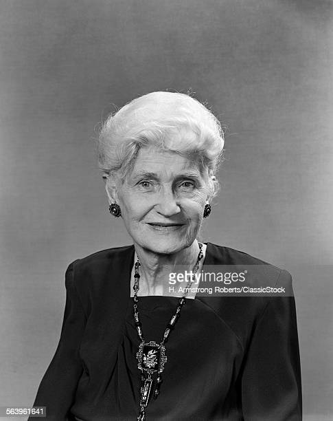1940s PORTRAIT OF SMILING ELDERLY WHITE HAIRED WOMAN WITH SQUARE NECKED BLACK DRESS AND ANTIQUE JEWELRY LOOKING AT CAMERA